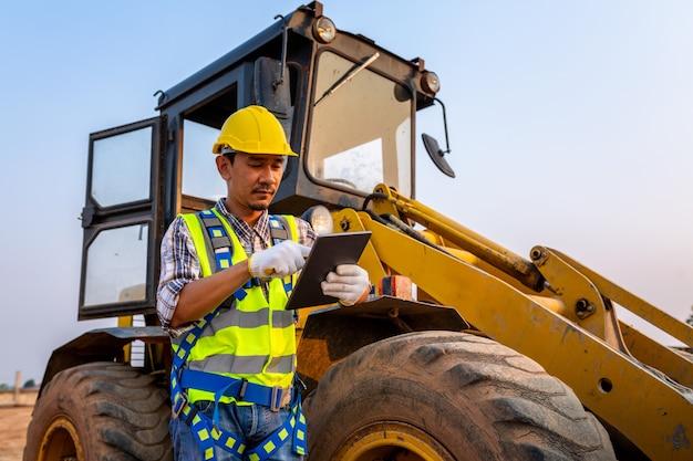 Drijvende werker met zware banden, werknemers drijven bestellingen door de tablet, wiellader graafmachine met graaflaadmachine die zand op de bouwplaats lost.