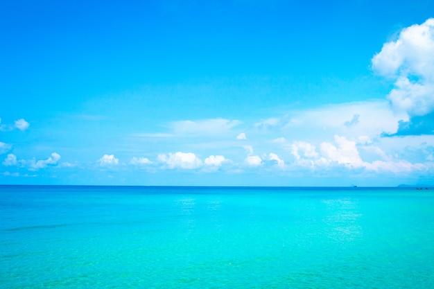 Drijvende wolken, donzige kleuren tegen de blauwe lucht en de zee