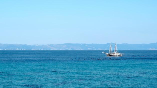 Drijvende zeilboot in de egeïsche zee met vogels op het oppervlak van het water ervoor en land griekenland