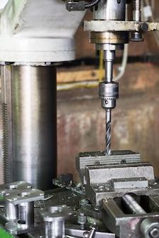 Dril machine. de boor wordt in de boorkop gemonteerd. machine bankschroef, metaalbewerkingswinkel.
