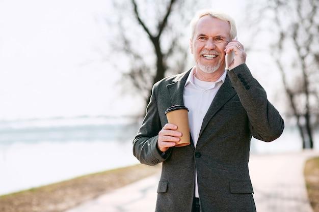 Drink en praat. gelukkig senior zakenman poseren in park en praten over de telefoon