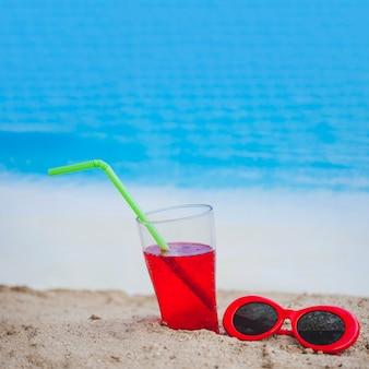 Drink en rode zonnebril op zanderig oppervlak