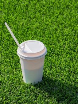 Drink in een papieren beker met rietjes op het voetbalveld.