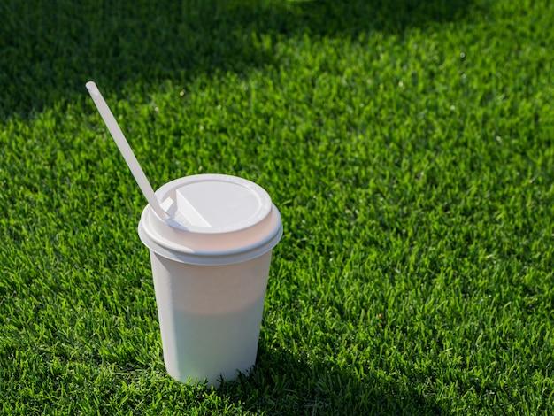 Drink in een papieren beker met rietjes op het voetbalveld