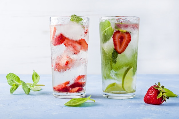 Drink met aardbei, limoen en munt. zomerlimonades of ijsthee. mojito cocktails met ijsblokjes.