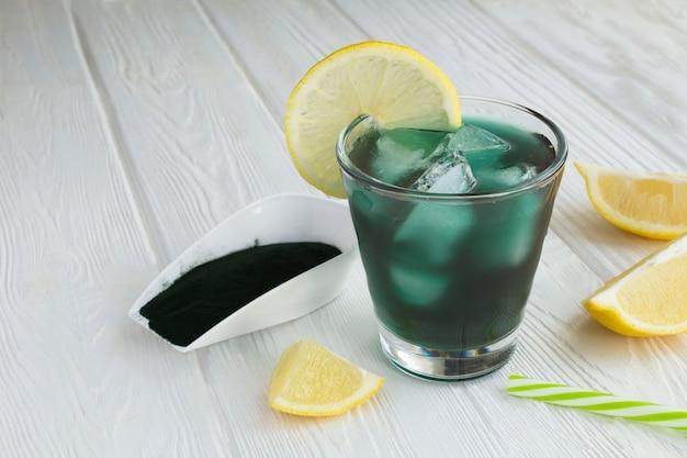 Drink met chlorella in het glas op het witte houten
