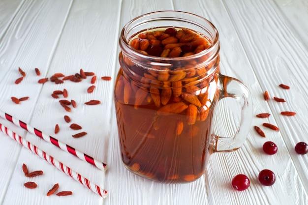 Drink met gojibessen en cranberry op de witte houten achtergrond