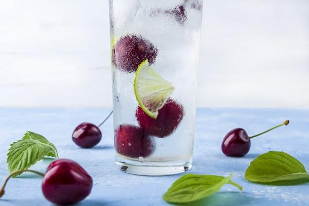 Drink met limoen, kers en munt. zomerlimonades of ijsthee. mojito cocktails met ijsblokjes.