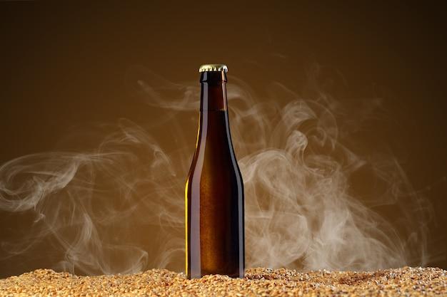 Drink mockup-serie. bruin bierflesje met reflecties die op tarwekorrels staat op een omber studioachtergrond met lichte rook. sjabloon klaar voor gebruik op uw ontwerp.