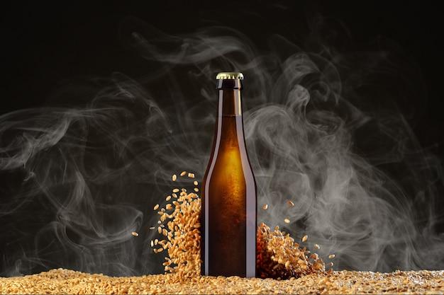 Drink mockup-serie. bruine bierfles met reflecties op een rookzwarte studioachtergrond met verstrooiende tarwekorrels. sjabloon klaar voor gebruik op uw vitrine.