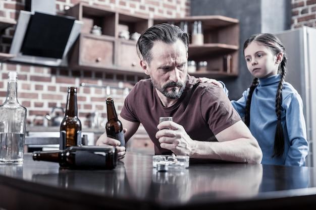 Drink niet alsjeblieft. triest leuk jong meisje dat achter haar vader staat en haar hand op vaders schouder legt terwijl ze hem vraagt te stoppen met drinken