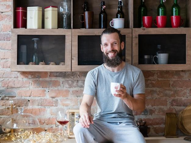 Drink 's ochtends warmte en energie. sta op en schijn. geluk. glimlachende bebaarde hipster zittend op het aanrecht met kop.