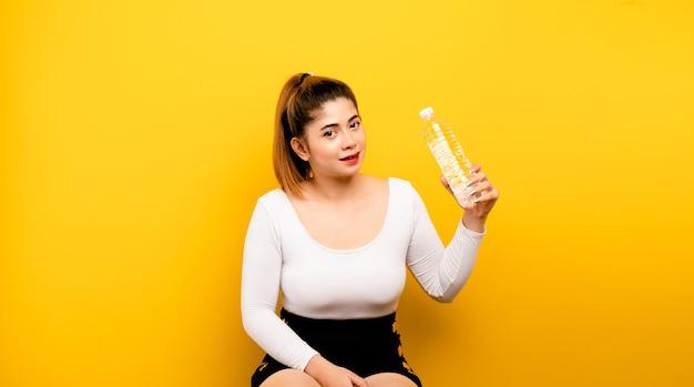 Drink schoon water. aziatische vrouw die water voorbereidingen treft te drinken. schoon uit de fles om de dorst te lessen en om een gezond drinkwaterconcept te behouden.