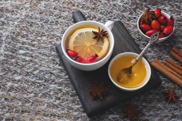 Drink van wilde rozen bessen met citroen en honing kaneel. vitamine nuttig aftreksel van rozenbottels. gezellig huis concept van winter drankje kopieer de ruimte
