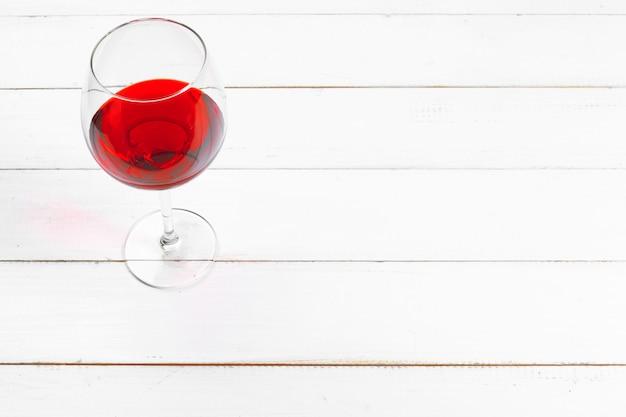 Drinkbeker rode wijn op houten lijst aangaande houten muurachtergrond