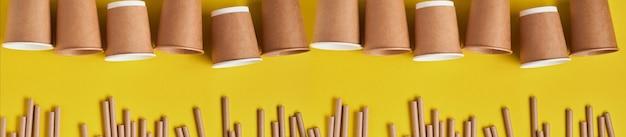 Drinkbekers gemaakt van papier en maizena, biologisch afbreekbaar materiaal en eco papieren glazen op gele trendkleur 2021 geen afval en plasticvrij concept. bovenaanzicht.