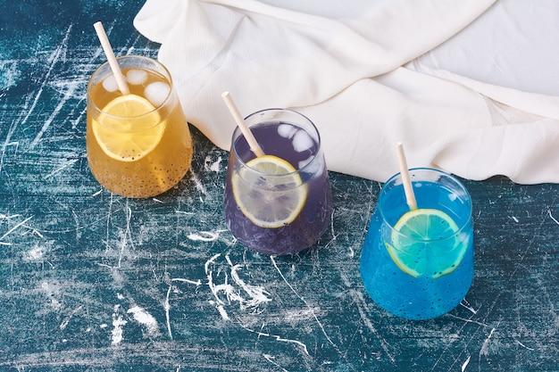Drinkbekers in drie verschillende kleuren op blauw.