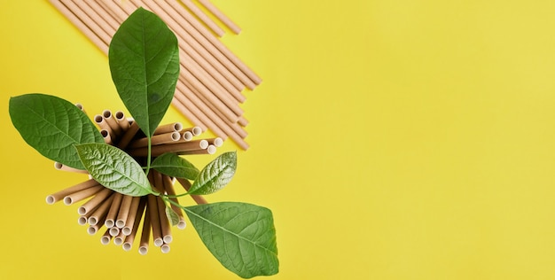 Drinkbuizen gemaakt van papier en maizena, biologisch afbreekbaar materiaal en eco papieren glazen met groene spruitblaadjes op gele trendkleur 2021 achtergrond. geen afval en plasticvrij concept. bovenaanzicht.