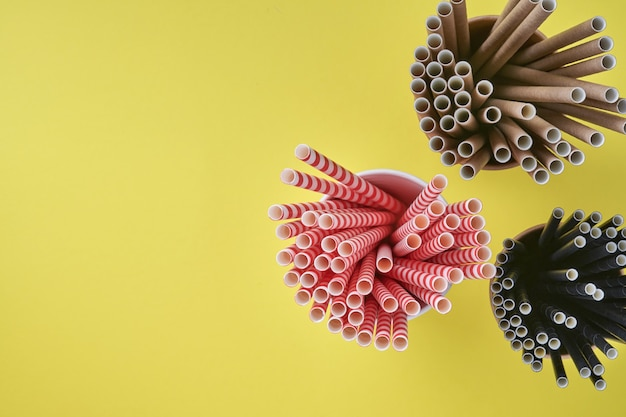 Drinkbuizen rood en bruin van papier en maizena, biologisch afbreekbaar materiaal en eco papieren glazen op geel en grijze trendkleur 2021 achtergrond. geen afval en plasticvrij concept. bovenaanzicht.