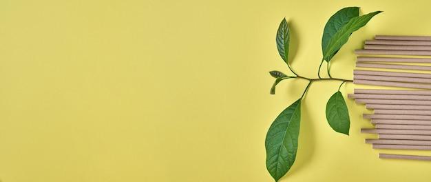 Drinkbuizen van papier en maizena, biologisch afbreekbaar materiaal en eco papieren glazen met groene spruitblaadjes op gele trendkleur 2021 zero waste en plasticvrij concept. bovenaanzicht.