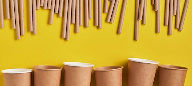 Drinkbuizen van papier en maizena, biologisch afbreekbaar materiaal en eco papieren glazen op gele trendkleur 2021 achtergrond. geen afval en plasticvrij concept. banner. bovenaanzicht.