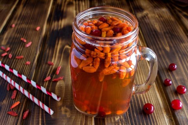 Drinken met gojibessen en cranberry op de bruine houten achtergrond