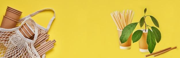 Drinken van bruine buizen rietjes gemaakt van papier en maizena, mesh marktzak en lege papieren koffiekopjes op een trendy gele achtergrond. geen afval en plasticvrij concept. bovenaanzicht.