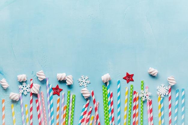 Drinken van papier kleurrijke rietjes voor nieuwjaarscocktails op lichtblauw oppervlak. kerstkaart.