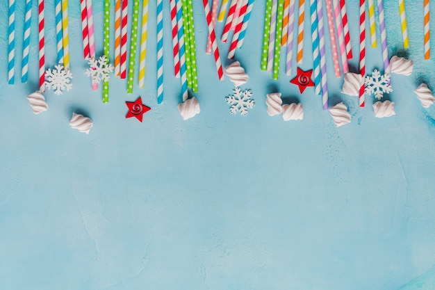 Drinken van papier kleurrijke rietjes voor nieuwjaarscocktails op lichtblauw oppervlak