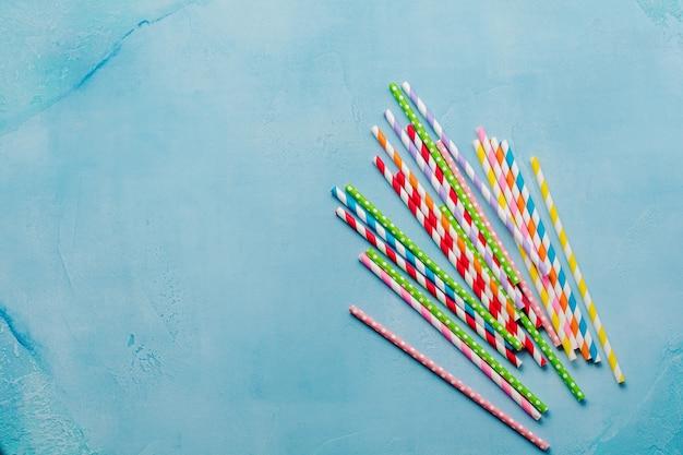 Drinkpapier kleurrijke rietjes voor zomercocktails op lichtblauwe achtergrond. bovenaanzicht.