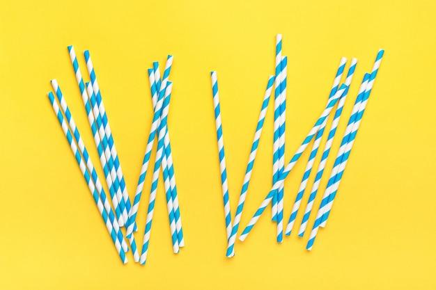 Drinkpapier rietjes voor feest met blauwe strepen, ijsblokje op gele achtergrond met kopie ruimte