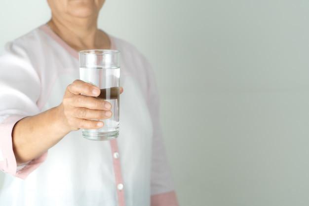 Drinkwater in de hand van de hogere vrouw, concept milieubescherming, gezonde drank.
