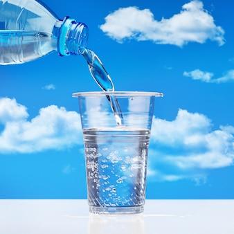 Drinkwater uit plastic fles gieten in glas, tegen blauwe hemel met wolken.