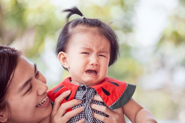 Droevig aziatisch babymeisje die en moeder schreeuwen die haar troosten met liefde