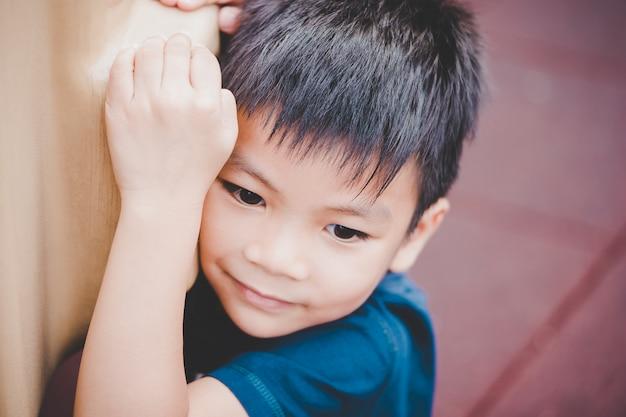 Droevig aziatisch jongensportret bij het spelen in speelplaats