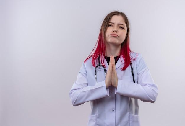 Droevig jong artsenmeisje die stethoscoop medisch kleed dragen die bidgebaar op geïsoleerde witte achtergrond met exemplaarruimte tonen