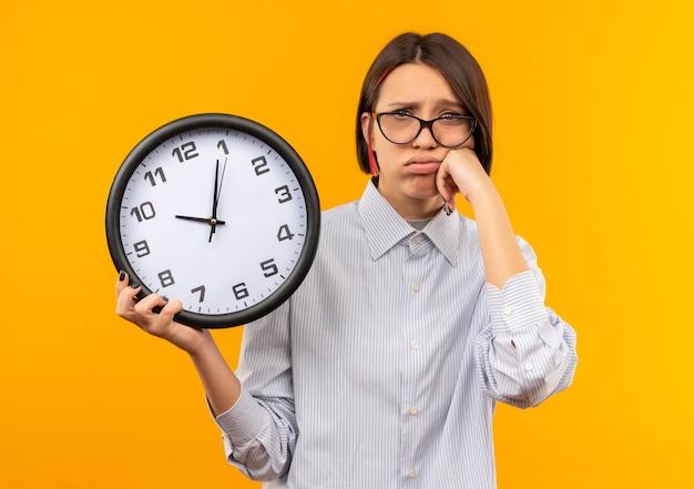 Droevig jong call centreermeisje die glazen dragen die klok houden die hand op wang zetten die op oranje muur wordt geïsoleerd