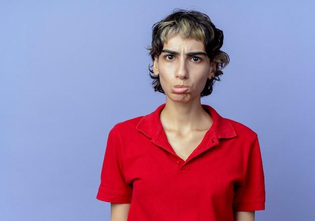 Droevig jong kaukasisch meisje met pixiekapsel die camera bekijken die op purpere achtergrond met exemplaarruimte wordt geïsoleerd