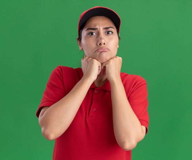 Droevig jong leveringsmeisje die eenvormig en glb dragen die vuisten onder kin zetten die op groene muur wordt geïsoleerd