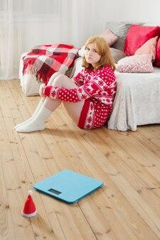 Droevig jong meisje in kerstmissweater met blauwe schaal voor gewichtsbeheersing thuis