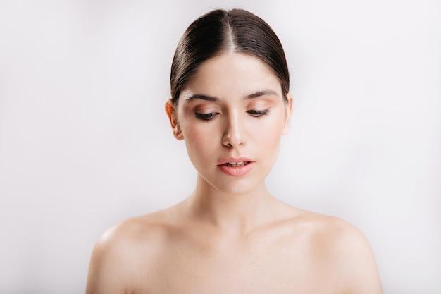 Droevig jong meisje met schone huid zonder make-up op haar gezicht vormt voor portret op geïsoleerde muur.