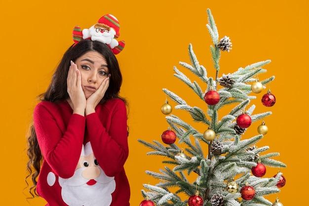 Droevig jong mooi meisje dat de hoofdband en de sweater van de kerstman draagt