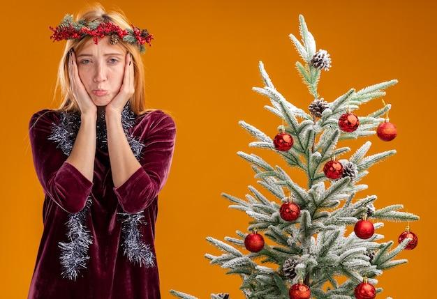 Droevig jong mooi meisje dat in de buurt van de kerstboom staat met een rode jurk en een krans met een krans op een nek bedekt gezicht met handen geïsoleerd op een oranje muur