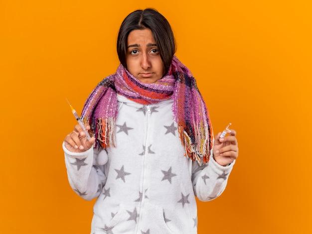Droevig jong ziek meisje die de spuit van de sjaalholding met ampul dragen die op gele achtergrond wordt geïsoleerd
