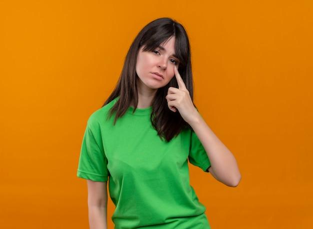 Droevig kaukasisch meisje in groen shirt legt hand op gezicht en kijkt naar camera op geïsoleerde oranje achtergrond