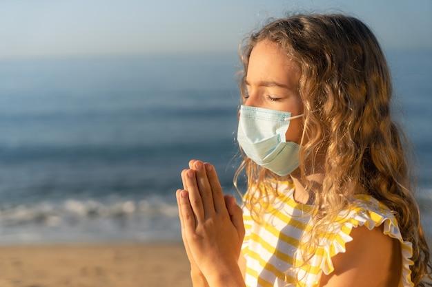 Droevig kind dat medisch masker buiten tegen blauwe hemel draagt.