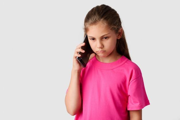 Droevig klein meisje dat op moderne mobiele telefoon spreekt