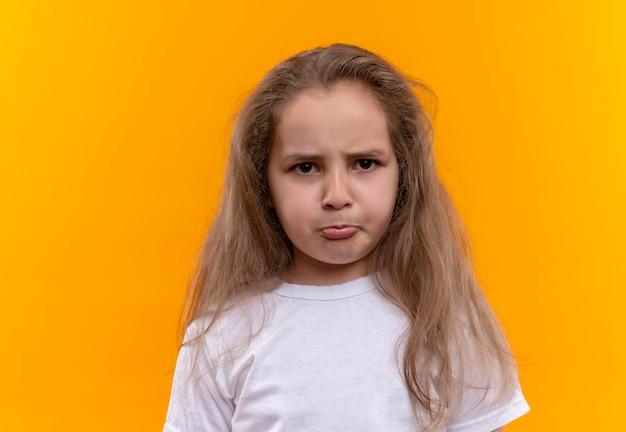 Droevig klein schoolmeisje dat wit t-shirt op geïsoleerde oranje achtergrond draagt