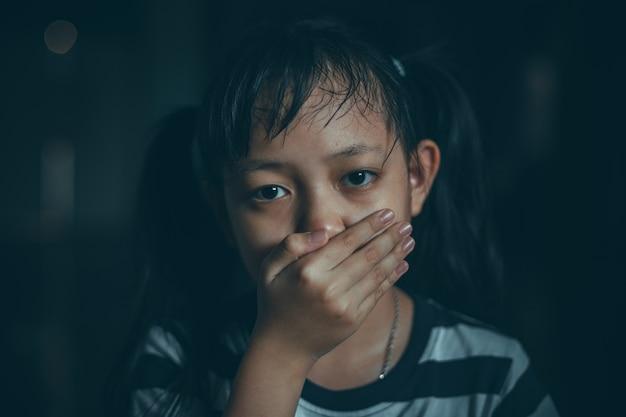 Droevig meisje dat haar mond behandelt met hand