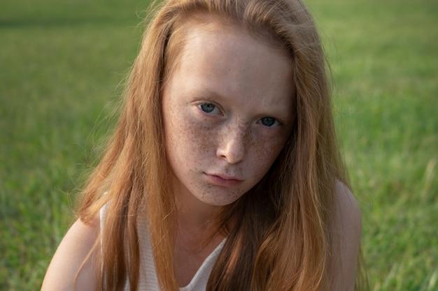 Droevig meisje dat in camera met ongelukkige ogen kijkt